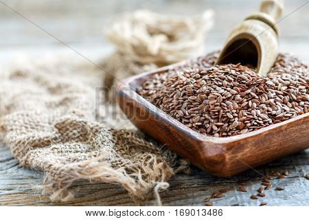 Brown Flax And Wooden Scoop In A Square Bowl.