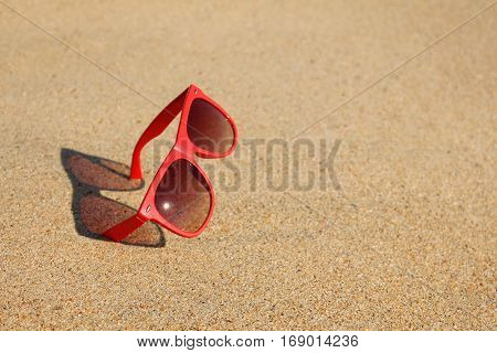 Red sunglasses in the sand at the beach, Summer vacation concept with copy space.