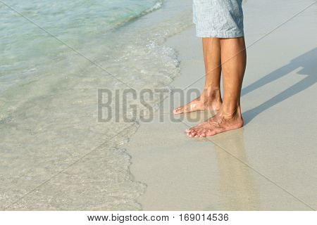 View of feet on a white sand beach, Thailand
