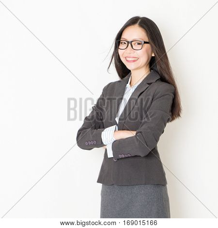 Portrait of Asian businesspeople in formalwear smiling and looking at camera, standing on plain background.