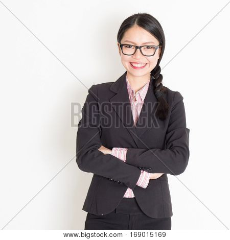 Portrait of Asian businesswoman in formalwear smiling and looking at camera, standing on plain background.