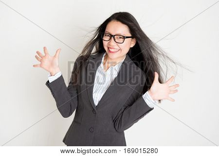 Portrait of happy Asian businesswoman in formalwear smiling and palms open, standing on plain background.