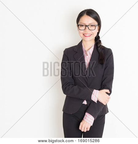 Asian businesswoman in formalwear smiling and looking at camera, standing on plain background.