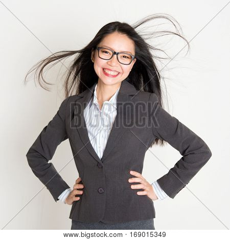 Portrait of Asian businesswoman in formalwear smiling and hands on waist, standing on plain background.