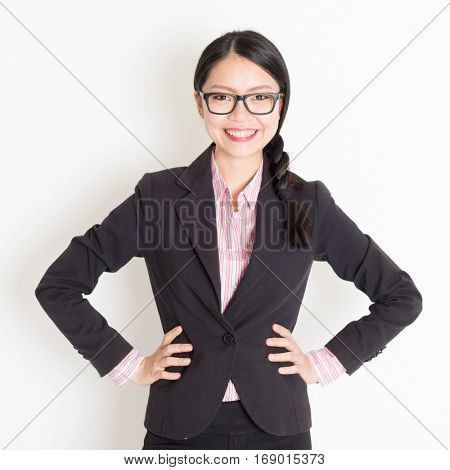 Portrait of Asian business woman in formalwear smiling and looking at camera, standing on plain background.