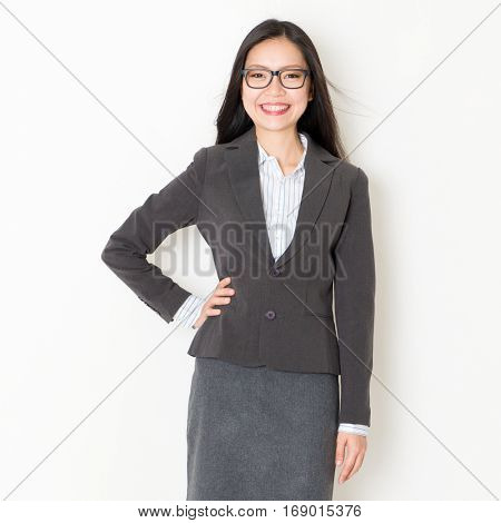 Portrait of young Asian business people in formalwear smiling and looking at camera, standing on plain background.