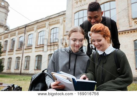 Multiethnic group of happy young people reading book outdoors at the unversity campus