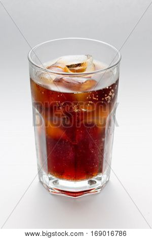 Misted glass with a glass of Coke, Pepsi, rum, cocktai, alcohol ice cubes on a white background