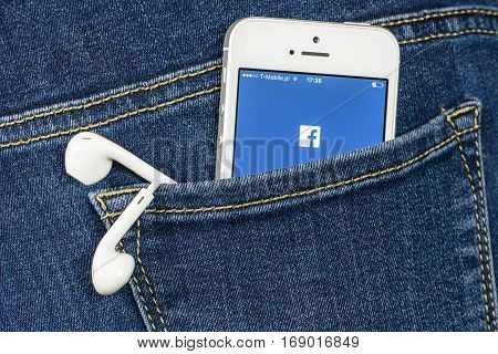Krynica Poland - February 02 2017: Facebok app on iPhone SE screen in blue jeans pocket. Facebook is one of the most popular social media service app on the world.
