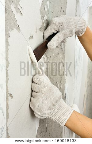hands removing wallpaper from wall with spatula