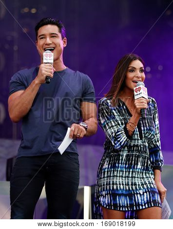 LAS VEGAS-SEP 20: TV personality Mario Lopez (L) and wife Courtney Lopez on stage at the 2014 iHeartRadio Music Festival Village Show at MGM Resorts Village on September 20, 2014 in Las Vegas, Nevada.