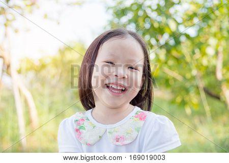 Little cute asian girl smiling in park
