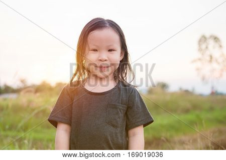 Little asian girl smiling in park with sunset