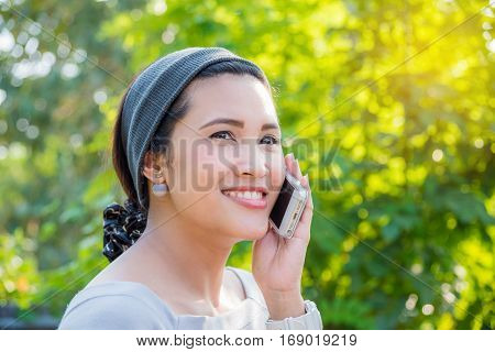 Beautiful asian woman calling someone by cellphone
