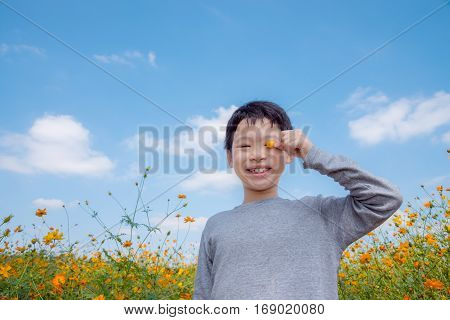 Young asian boy smiling in flower field