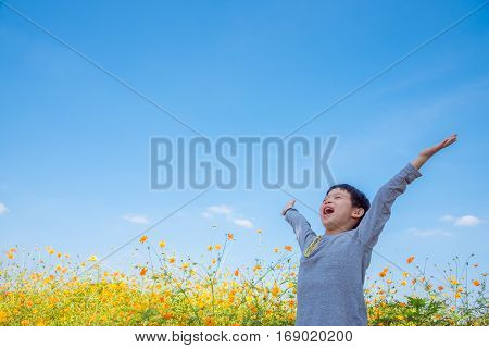 Young asian boy happy at flower field