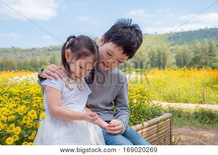 Young Asian boy is comforting his crying sister in park