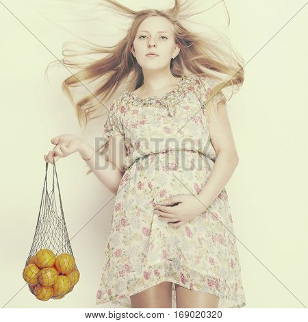 Pregnant woman holding fruits.  Nutrition and diet during pregnancy. Beautiful pregnant woman standing with oranges.