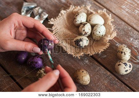 Decorating eggs for Easter holiday close up. Top view on hands coloring eggs. Tradition, handmade, hobby, art , craftmanship concept