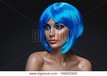 Beautiful young woman with glowing skin, fashion smokey make-up in short blue hair wig. Beauty shot on black background. Copy space.