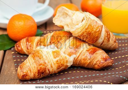 Fresh croissant and tangerines on wooden table horizontal