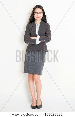 Portrait of Asian female businesswoman in formalwear smiling, full body standing on plain background.