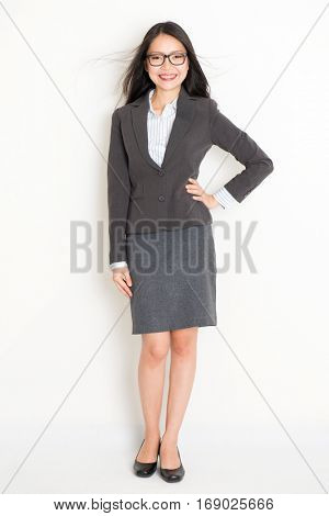 Portrait of young Asian female businesspeople in formalwear smiling, full body standing on plain background.