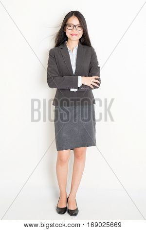 Portrait of young Asian businesswoman in formalwear smiling, full body standing on plain background.