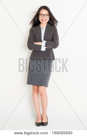 Portrait of Asian female business woman in formalwear smiling, full body standing on plain background.