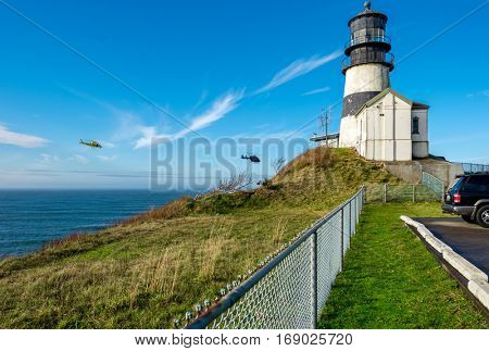 Cape Disappointment Lighthouse, built in 1856, Pacific coast, WA, USA. Coast guard helicopters in the sky.
