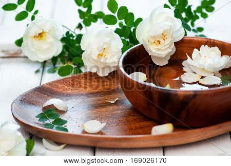 Aroma spa set with white roses and wooden bowl selective focus horizontal