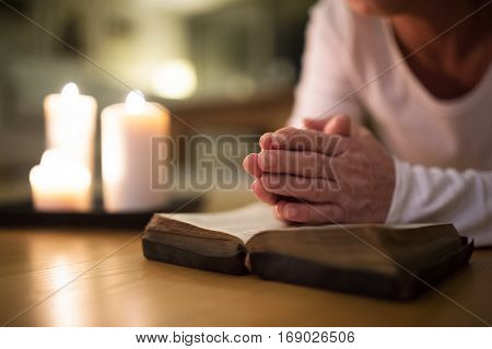 Unrecognizable senior woman lying on the floor praying with hands clasped together on her Bible. Burning candles next to her. Close up.