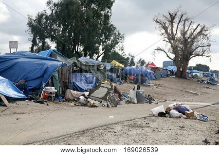 ANAHEIM, CA - JANUARY 9, 2017 Homeless encampment lined up along the Los Angeles River along a bike trail.