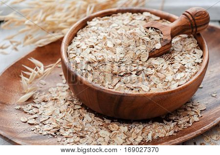 Raw cereal in wooden bowl and crop on white table selective focus vertical