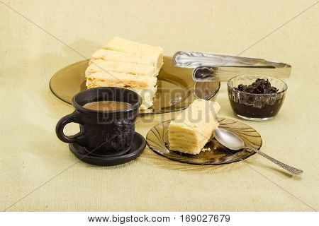 One piece of layered sponge cake on a glass saucer with spoon several pieces of cake on glass dish coffee with milk in black cup and jam on a cloth surface