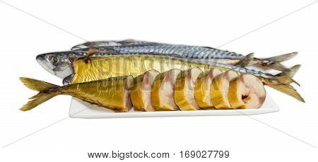 Sliced and whole cold-smoked Atlantic mackerel on a white dish against the backdrop of uncooked fish on a light background