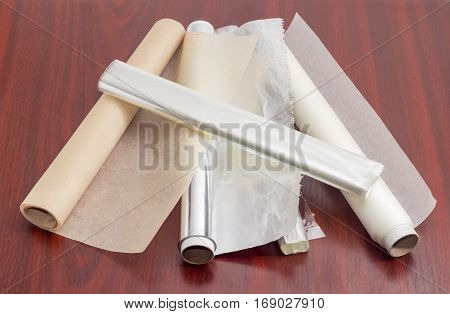 Two rolls of the various parchment paper two rolls of the plastic oven bags and one roll of the aluminum foil for household use on a dark red wooden surface