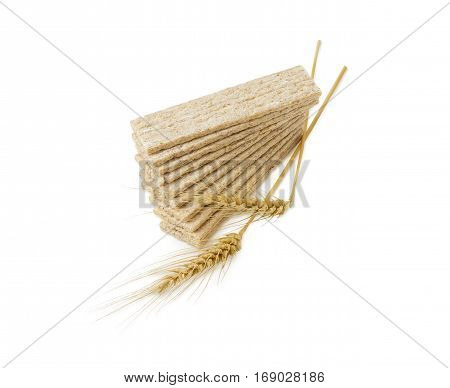 Pile of the dietary wheat wholegrain crispbread with adding the buckwheat and the barley and two wheat spikes on a light background