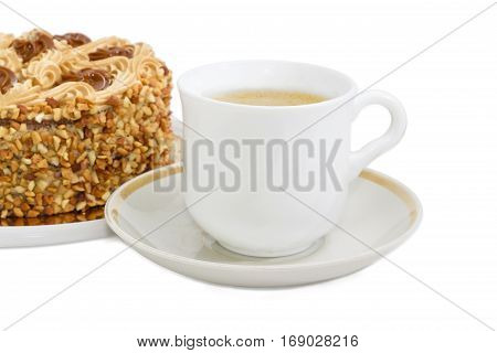 White cup with coffee with cream on a background of sponge cake decorated with butter cream and sprinkled with grated nuts on a light background