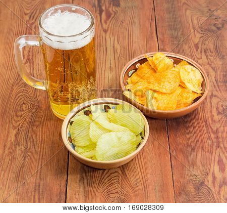 Glass tankard with lager beer potato chip flavored paprika and wasabi in two different ceramic bowls on an old wooden planks
