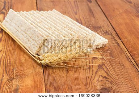 Several dietary wheat wholegrain crispbread with adding a buckwheat and a barley and two wheat spikes closeup on a surface of an old wooden planks