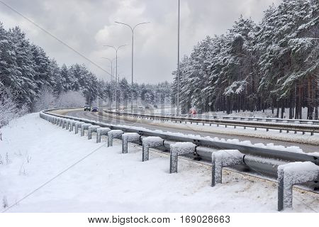 Part of the motorway with cars traffic barriers lampposts and pine forest covered snow on both sides of road after snowfall in cloudy day