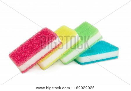 Several synthetic layered cleaning sponges with layer for more intense scrubbing different colors on a light background