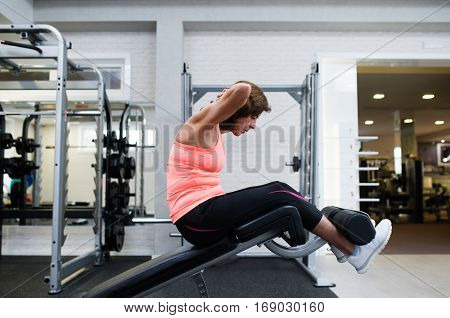 Beautiful fit senior woman in gym in sports clothing working her abs, doing abdominal crunches.