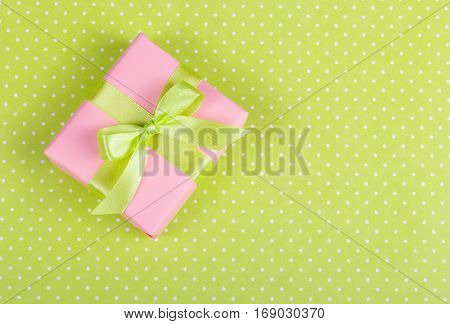 Pink gift box with a bow on a light green background. Box with surprise on a polka dot background. Copy space.