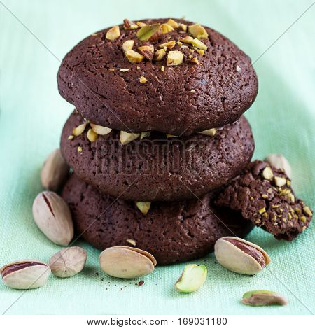 Homemade chocolate cookies with pistachios over green selective focus