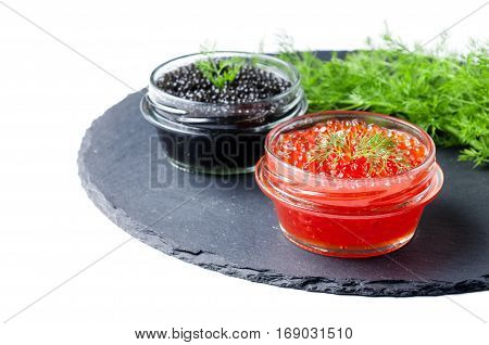 Close up of red and black caviar in jar on stone plate dill in background isolated on white selective focus horizontal