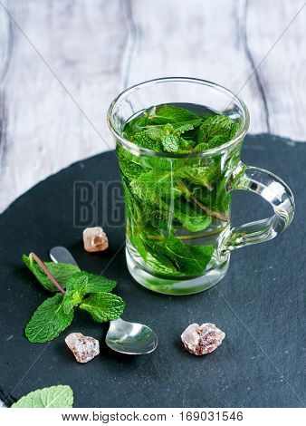 Fresh organic mint in glass on wooden background selective focus