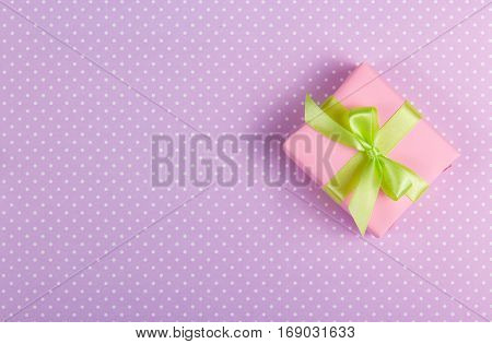 Little present with a bow on a gentle purple background. Gift Box on a polka dot background. Copy space
