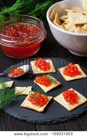 Biscuits salty crackers with red caviar on slate plate vertical selective focus